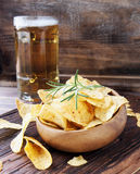 Chips in a wooden bowl and beer Stock Images