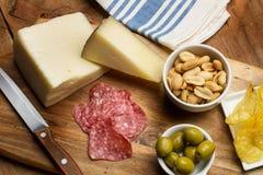 Chips, Wurst, Käse, Oliven auf einem Holztisch Lizenzfreies Stockbild