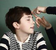 Chiquenaude de secousse obtenue par garçon sur son front photos libres de droits