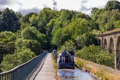 Chirk Aqueduct & Viaduct, Wrexham, Wales, UK. Chirk, Wrexham, Wales, UK - August 31, 2016: Narrowboats with people steering over the Chirk Aqueduct into the royalty free stock photos