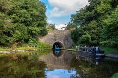 Chirk, Wrexham, Wales, UK. August 31, 2016: People steering a narrowboat out of the Chirk Tunnel, with other people on a boat waiting for them to pass by Royalty Free Stock Image