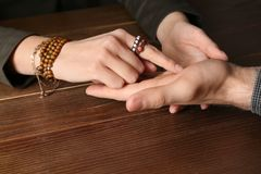 Chiromancer reading lines on man`s palm at table. Closeup stock photos