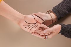 Chiromancer reading lines on woman`s palm against color background. Top view royalty free stock image