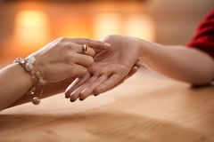 Chiromancer reading lines on woman`s palm at table. Closeup royalty free stock images