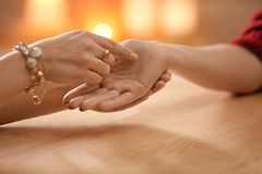 Chiromancer reading lines on woman`s palm at table. Closeup royalty free stock photography