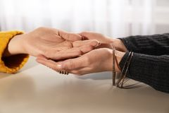 Chiromancer reading lines on woman`s palm at table. Closeup stock photo