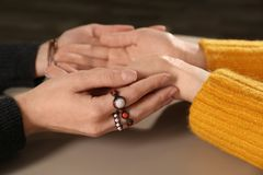 Chiromancer reading lines on woman`s palm at table. Closeup stock image