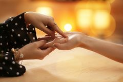 Chiromancer reading lines on woman`s palm at table. Closeup royalty free stock photos