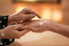 Chiromancer reading lines on woman`s palm at table. Closeup royalty free stock photo