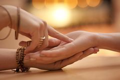Chiromancer reading lines on woman`s palm at table. Closeup stock photography