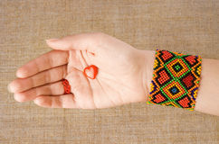 Chiromancy. Love on lifeline. Chiromant's hand with whicky holding red heart Royalty Free Stock Photography