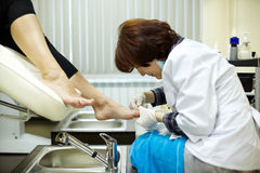 Chiropody master processes nails of client Royalty Free Stock Images