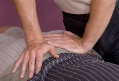 Chiropractic adjustment IV. Chiropractors hands giving spinal adjustment Royalty Free Stock Photo