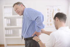 Chiropractic: Chiropractor examining senior man. stock photos