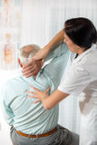 Chiropractic: Chiropractor examining senior man at office Royalty Free Stock Photo