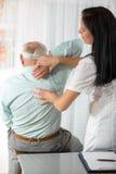 Chiropractic: Kiropraktor som undersöker den höga mannen på kontoret arkivbild