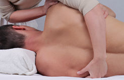 Chiropractic, osteopathy, pain relief concept. Dorsal manipulation therapist  doing healing treatment on man back Stock Photo