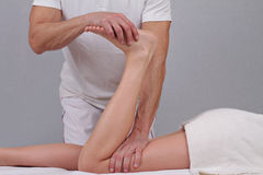 Chiropractic, osteopathy, sport massage concept. Therapist  doing healing treatment on female leg Stock Photos