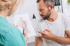 chiropractic showing human body picture to male patient during appointment