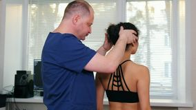 Chiropractic treatment - the doctor working with young woman`s neck to the sides stock footage