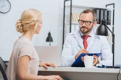 chiropractic in white coat making notes in notepad with female patient near by at table during appointment