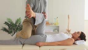 Chiropracticus en vrouw die speciale oefeningen doen stock footage