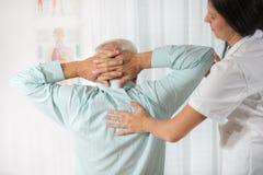 Chiropractie : Chiroprakteur examinant l'homme supérieur au bureau Images stock