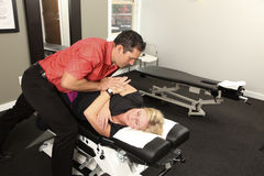 Chiropractor. Adjusting a female patient Stock Photos
