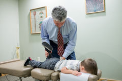 Chiropractor Adjusting Child in Office Royalty Free Stock Image
