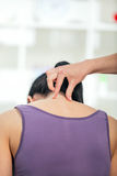 Chiropractor adjusting neck muscles to female Royalty Free Stock Image