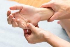 Chiropractor applying pressure on palm of female hand. stock photo