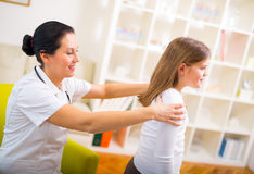 Chiropractor doing adjustment on female patient Stock Photos