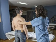 Chiropractor doing a visual exploring, static, dynamic position, scoliosis, kyphosis. Dynamic evaluation of scapular tilt during. An abduction stock image