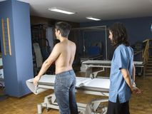 Chiropractor doing a visual exploring, static, dynamic position, scoliosis, kyphosis. Dynamic evaluation of scapular tilt during. An abduction stock images