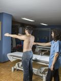 Chiropractor doing a visual exploring, static, dynamic position, scoliosis, kyphosis. Dynamic evaluation of scapular tilt during. An abduction stock photography