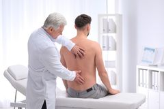 Chiropractor examining patient with back pain. In clinic stock image
