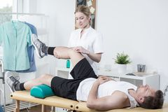 Chiropractor exercising man's leg. Horizontal view of female chiropractor exercising man's leg Royalty Free Stock Images