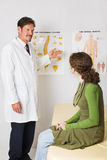 Chiropractor Explains Spinal Column. Chiropractor using *generic* charts to explain the spinal column to a patient Stock Photography