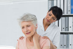 Chiropractor looking at senior woman with neck pain Royalty Free Stock Images
