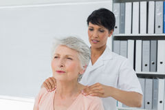 Chiropractor massaging a senior womans shoulder Stock Image
