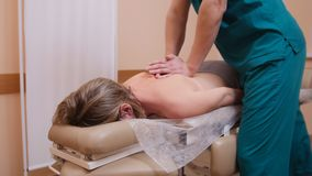 Chiropractor massaging a woman lying on a massage table, flexing the shoulder. Chiropractor massaging a women lying on a massage table, flexing the shoulder royalty free stock photos