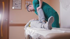 Chiropractor massaging a young woman lying on a massage table, stretching and flexing her hip joint pressing on her knee stock footage