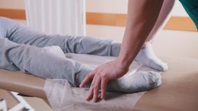 Chiropractor massaging a young woman lying on a massage table, stretching her feet stock video