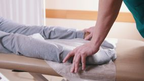Chiropractor massaging a young woman lying on a massage table, stretching her feet, close-up of legs stock video footage