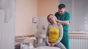 Chiropractor massaging a young woman bending and turning her neck in the medical office stock video footage