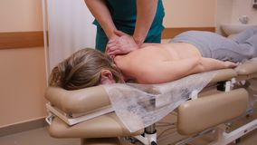 Chiropractor massaging a young woman lying on a massage table, pushing on her back with his elbow, spine model and drugs royalty free stock photos