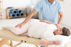 Chiropractor performing back adjustment. Chiropractor performing back bones adjustment on a senior women lying on a table in rehabilitation stock images
