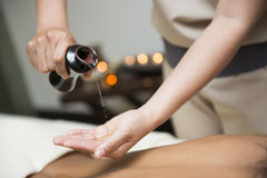Chiropractor pour oil into hand for massage. Oil massage stock photography