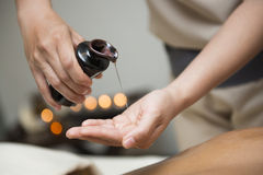 Chiropractor pour oil into hand for massage. Oil massage stock image