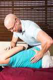Chiropractor press female patient lower back Stock Photography